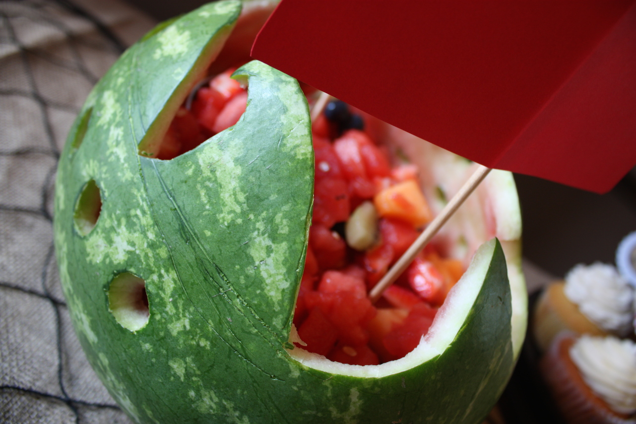 Melon cut into a pirate ship shape and overflowing with fruit doubles as more pirate decoration.