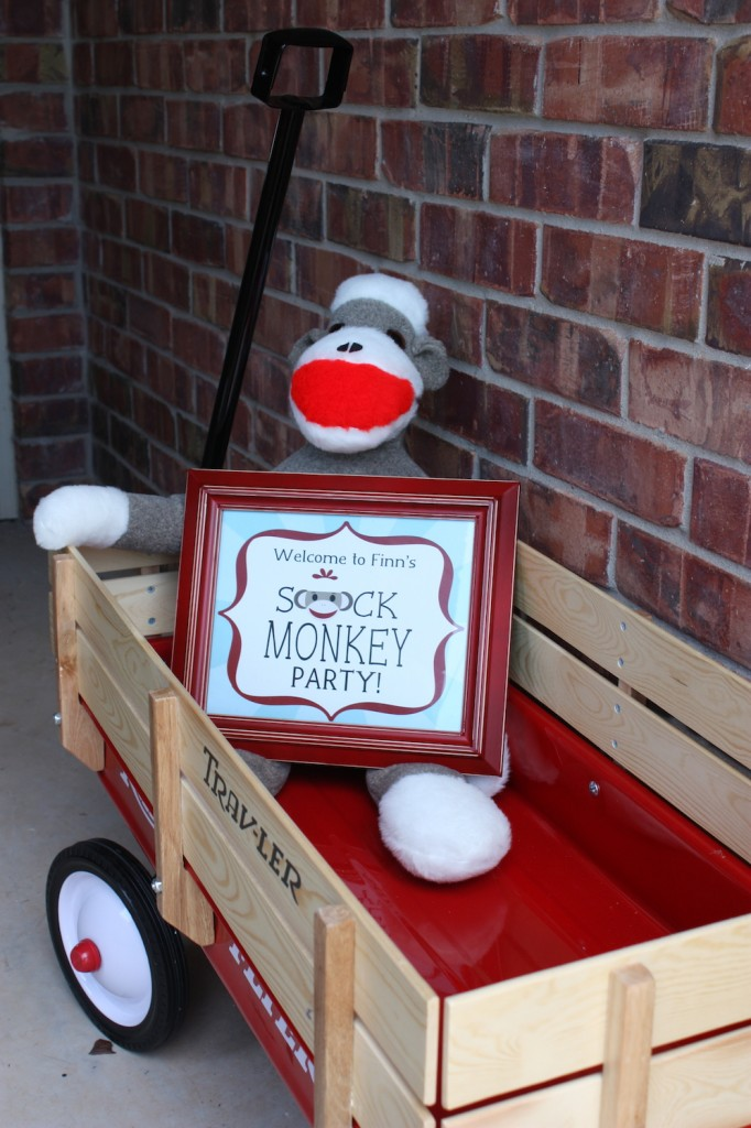 The birthday boy got a red trav-ler wagon for his first birthday. We bought this massive travesty of a fake sock monkey for about a quarter of the price of a real one. The sign came with our printable set from Designing for Peanuts and we put it in a red frame from Hobby Lobby.