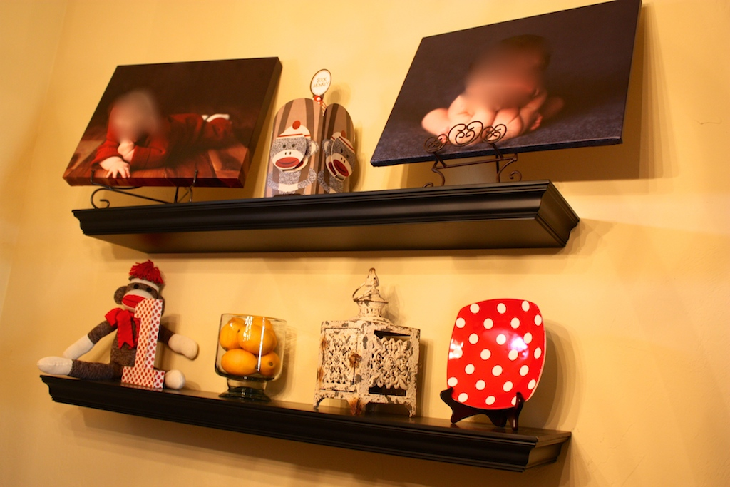Shelving with newborn and three month photo canvases, sock monkey and red and white polkadot number one and plate.